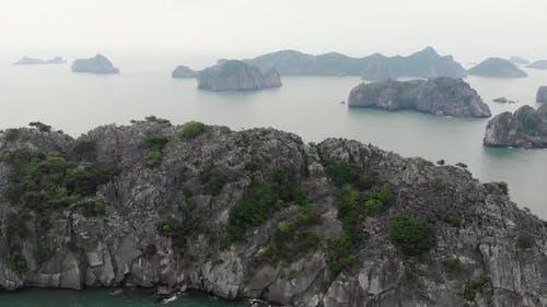 Aerial: flying over Cat Ba and Ha Long Bay rock pinnacles at sunset, travel destination Vietnam