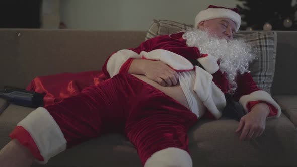 Thumbnail for Bad Santa Claus Sleeping on Sofa and Scratching His Belly. Empty Bottle Lying Next To Him on the