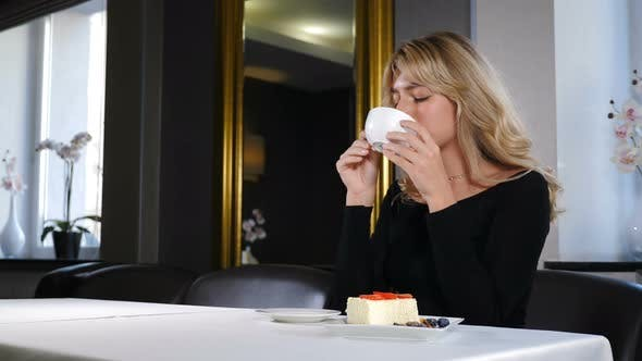 Portrait of Relaxed Girl Having Coffee Break. Beautiful Romantic Girl with Cup of Coffee or Tea