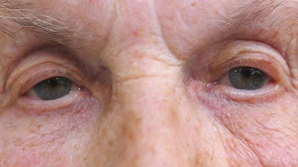 Thumbnail for Portrait of Elderly Woman Watching Pensive Into Camera and Blinking. Close Up of Wrinkled Female