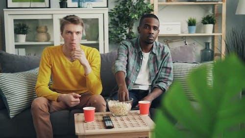 Verärgerte junge Männer Afroamerikanische und kaukasische Freunde schauen mit emotionlosem Fernsehen