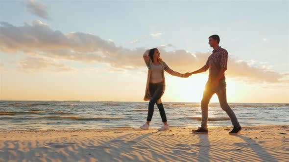 Thumbnail for Steadicam Shot: Loving Couple Walking at Sunset on the Beach or Lake. She Leads the Guy Flirting