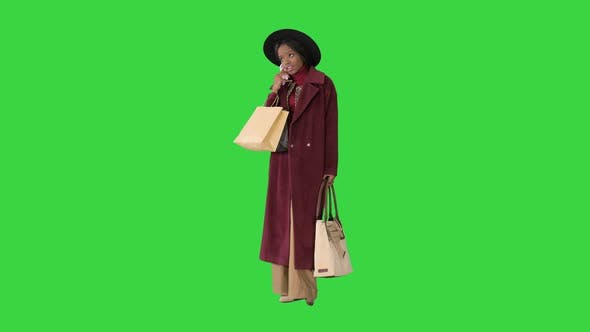 Thumbnail for Happy Young Black Girl Using a Mobile Phone Making a Call on a Green Screen, Chroma Key.