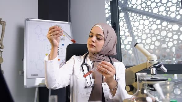 Thumbnail for Muslim Female Doctor in Hijab Comparing Chemical Liquids in Two Test Tubes in the Clinic Laboratory
