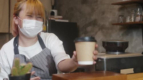 Young Asia female barista serving take away hot coffee paper cup to consumer.