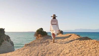 Stylish Boho Woman Walking on Cliff Over Mediterranean Sea