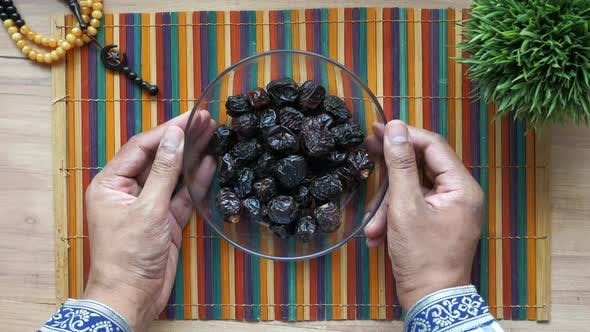 the Concept of Ramadan Hand Pick Date Fruit From a Bowl