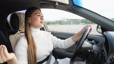 Fashionable Model in White Sings Holding Car Steering Wheel