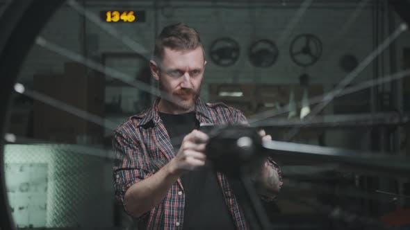 Ein junger männlicher Radfahrer macht Bilder von einem Fahrzeugrad, um es zu verkaufen oder ein Ersatzteil zur Reparatur zu finden