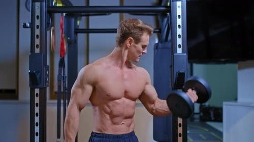 Professional Athlete Shakes the Biceps of the Arms with the Help of Dumbbells, Raises the Dumbbells