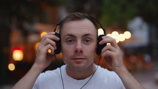 Man Puts on Big Headphones in the Evening City