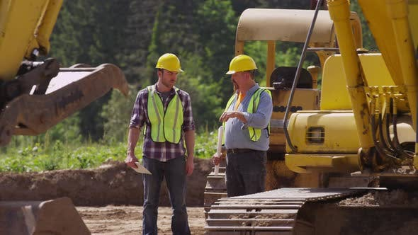 Thumbnail for Two workers talking by machinery
