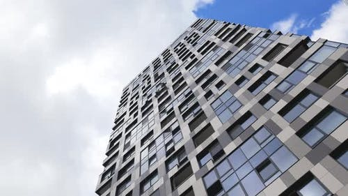 Industrial Climbers Cleaning the Exterior Windows of a Skyscraper with Blue Sky and Clouds on
