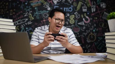 Young teacher is playing games on mobile phone likes crazy