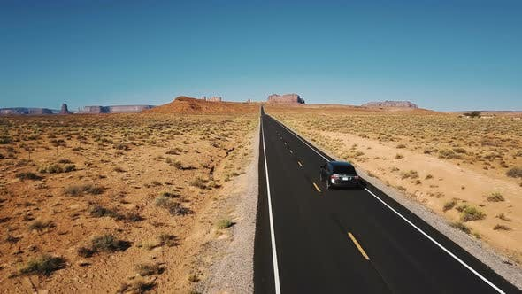 Thumbnail for Beautiful Aerial Shot of Silver Car Driving Along Amazing American Desert Road Towards Mountains in