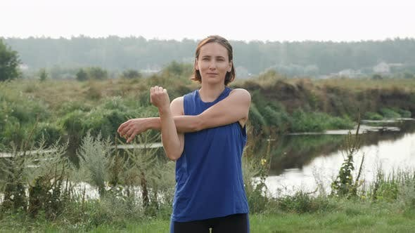 Active woman stretching outdoor after running training.