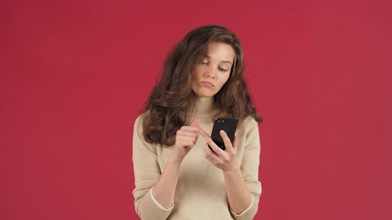 Portrait of Caucasian Woman with Long Hair Stands on Red Background in Studio Holds Phone in Hands