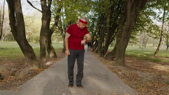 Senior Old Man Running in Park and Using Smart Watch, Tracking Result During Fitness Workout