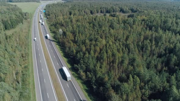 Convoy of Trucks Ride on the Highway Near Forest, Logistic Transportation, View of the Road From