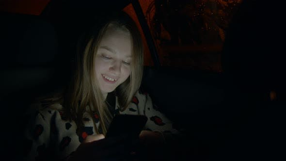 Young Smiling Woman in the Backseat of a Car and Looking at the Phone
