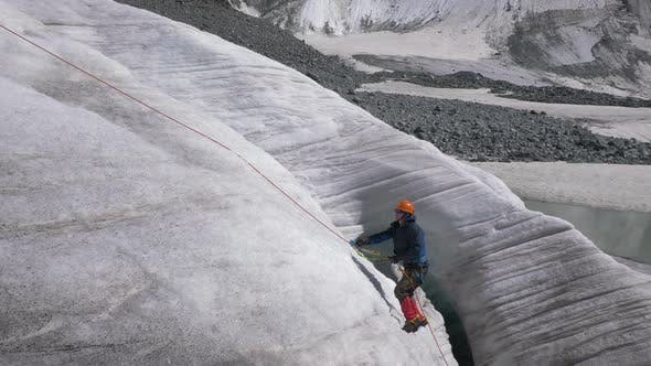 Thumbnail for Mountaineer Man in Crampons Is Using Ascender on Fixed Rope on Steep Slope in Mountains