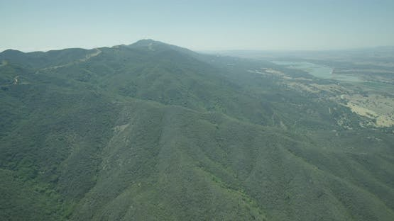 Steady helicopter aerial shot of hilly topography, cloudy day