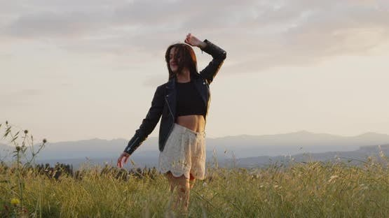 Young woman enjoying life and freedom at the land at sunset.