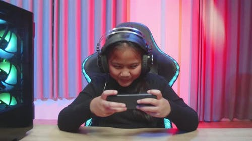 Happy Girl Focused On Playing Video Games On Her Smartphone