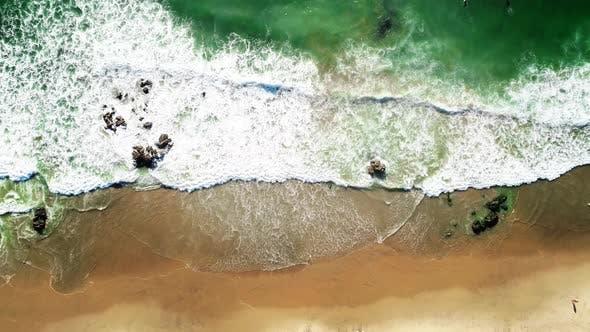 Grandes vagues de l'océan avec rouleau de mousse blanche sur la plage jaune