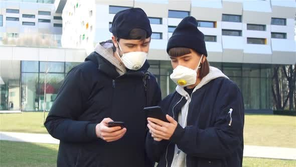Thumbnail for Couple Checking News in Their Phones About Corona Virus Wearing Protective Masks