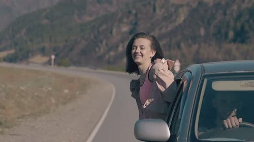 Automobile Speeds with Young Woman Leaning Out Car Window