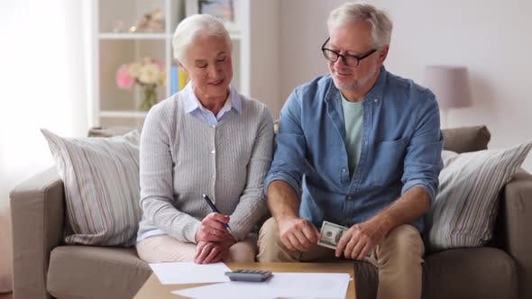 Senior Couple with Money and Bills at Home