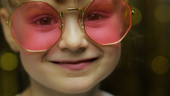 Thumbnail for Close Up Face of Child. Smiling, Looking at Camera. Girl in Pink Sunglasses Posing