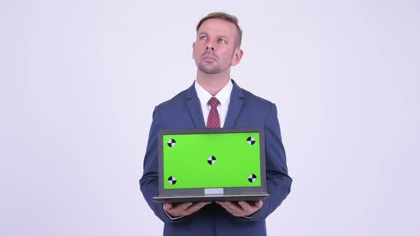 Thumbnail for Happy Blonde Businessman Thinking While Showing Laptop