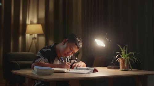 Asian Boy Is Studying At Home, Asia Child Writing While Sitting On The Table At Night