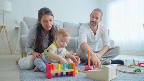 Caucasian happy family, loving parent play with baby toddler in living room enjoy activity at home.