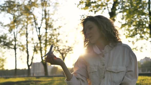 Thumbnail for Girl Plays with a Plane Sitting in the Park on the Grass at Sunset, Dreams of Traveling, Slow Motion