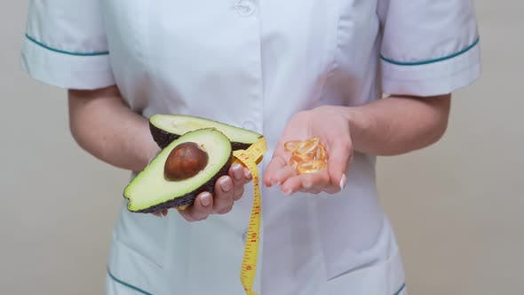 Cover Image for Nutritionist Doctor Healthy Lifestyle Concept - Holding Organic Avocado Fruit and Measuring Tape