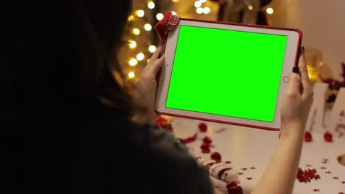 iPad tablet green screen. Woman watching, smiling for a Christmas wishes from her friends, parents