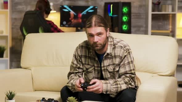 Thumbnail for Focused Bearded Man Sitting on Couch Playing Video Games