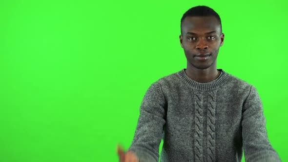 Thumbnail for A Young Black Man Waves at the Camera in a Gesture of Invitation - Green Screen Studio