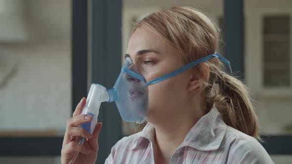 Woman Using Nebulizer for Respiratory Diseases Indoor
