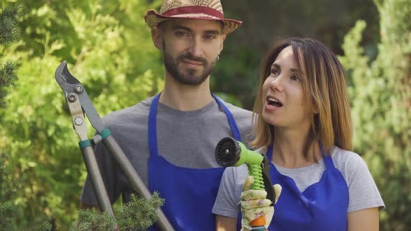 Thumbnail for Portrait Smiling Caucasian Woman and Handsome Man in Blue Uniform Standing in the Garden Holding