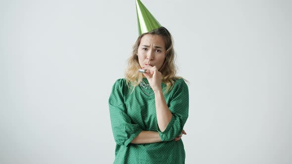 Portrait of Miserable Young Woman Wearing Party Hat Blowing Horn with Sad and Disappointed Face