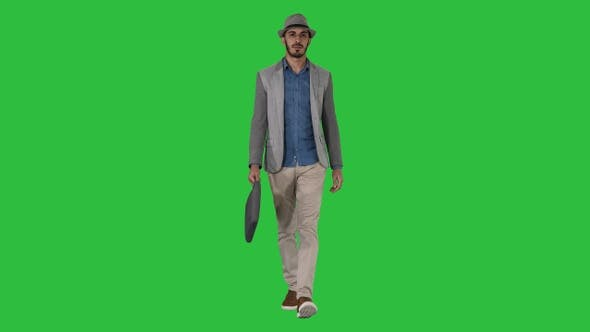 Thumbnail for Casual arabian man walking in a hat and with a briefcase