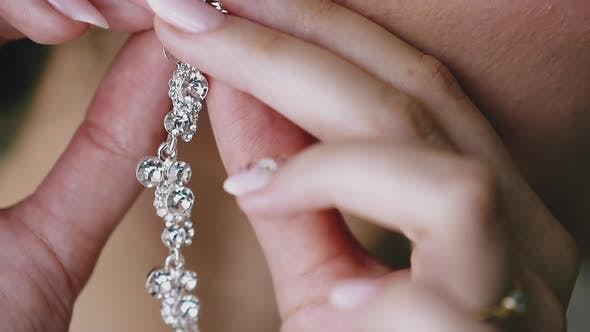Woman with Manicure Puts on Earring with Gems Closeup