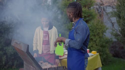 Side View Middle Shot of African American Man Blowing Smoke on Bbq As Teenage Girl Standing at