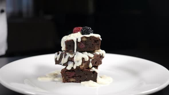 Thumbnail for Stack of Brownies Dessert Being Decorated with Berries on White Plate. Falling Berries in Slow