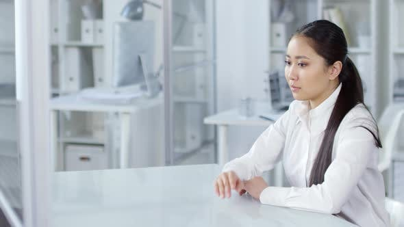 Thumbnail for Young Asian Woman Looking at Invisible AR Touchscreen in Office