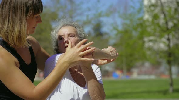 Thumbnail for Focused Elderly Lady with Coach Stretching Arm in Park